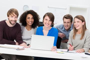 motivierte gruppe mit laptop am schreibtisch