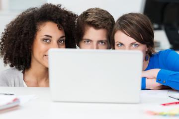 drei junge leute schauen über laptop