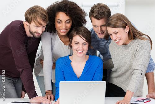 junge leute im büro schauen gespannt auf laptop