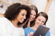 drei freundinnen schauen lachend auf tablet-pc