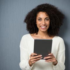 frau mit locken hält tablet in der hand