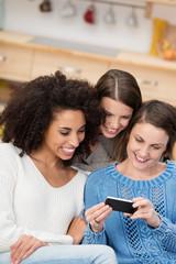 drei freundinnen zu hause schauen auf smartphone
