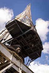 Old crane in docks with blue sky background.