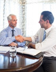 Businessmen shaking hands at office
