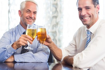 Happy business colleagues toasting beer glasses