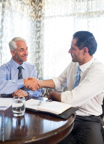 Businessmen shaking hands at office desk