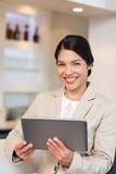 Smiling young businesswoman holding digital tablet