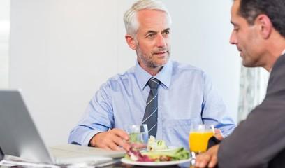 Businessmen using laptop while having food