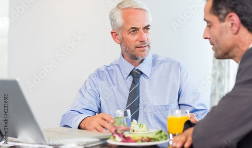 Businessmen using laptop while having food