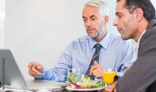 Two businessmen using laptop while having food