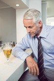 Tensed businessman with beer glass at bar counter