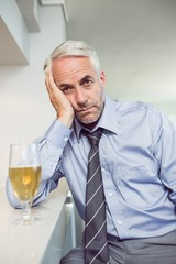 Tensed mature businessman with beer glass at bar counter