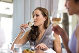 Woman having wine with friend at restaurant
