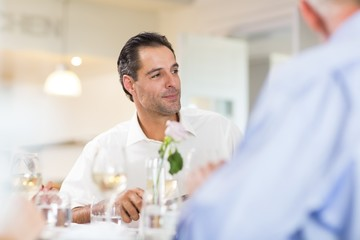 Handsome man having wine with friend at restaurant