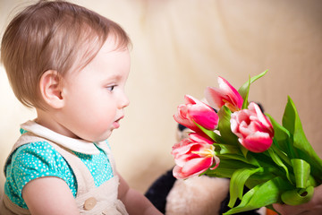 10 months old baby girl looking at flowers
