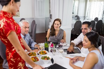 Waitress serving food to colleagues at dining table in restauran