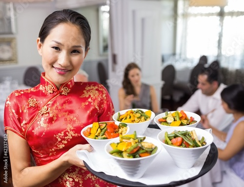 Waitress carrying food tray with people at dining table in