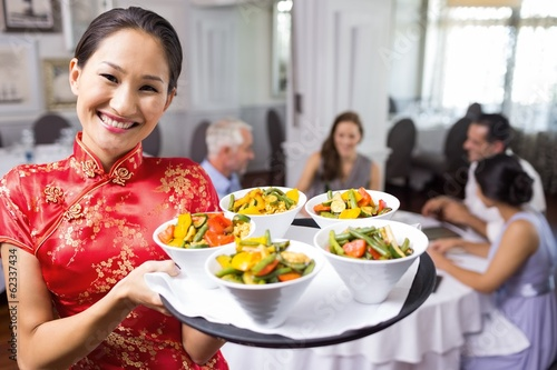 Waitress carrying food tray with people at dining table in resta