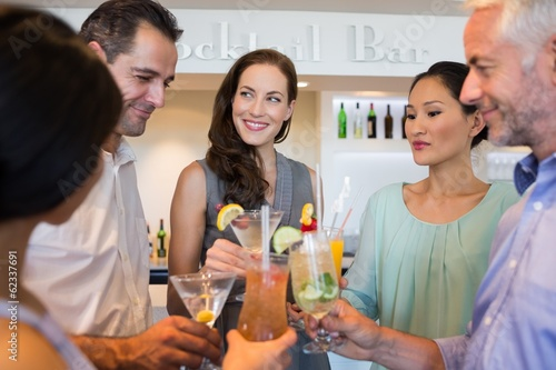 People toasting cocktails at the bar