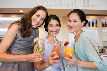 Cheerful women holding cocktail glasses