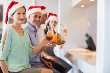 People in Santas hats with cocktail glasses at bar counter