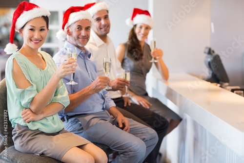 People in Santas hats with champagne flutes at bar counter