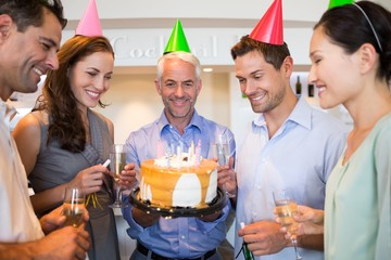 Group of people with champagne flutes and cake