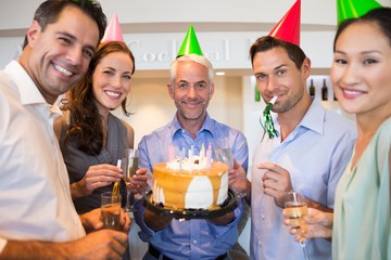 Happy group of people with champagne flutes and cake