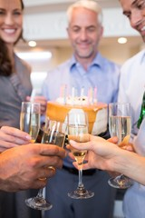 Closeup of people with champagne flutes and cake
