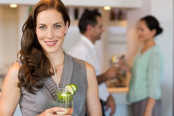 Smiling woman holding cocktail glass with friends at the bar