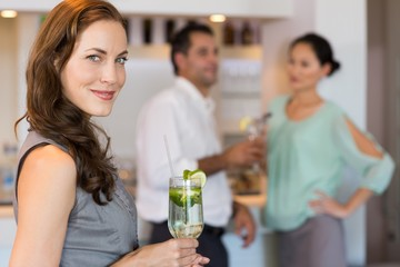 Smiling woman holding cocktail glass with friends in