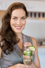Smiling young woman holding cocktail glass