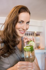 Closeup of a smiling young woman holding cocktail glass