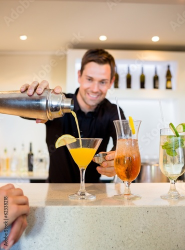 Smiling bartender preparing a drink at bar counter