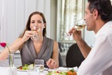 Couple drinking wine at dining table in restaurant
