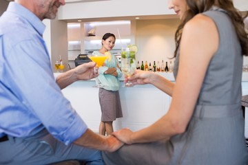 Cropped couple toasting cocktails with woman in background