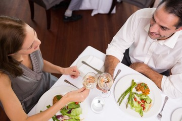 Couple toasting wine glasses at dining table in restaurant