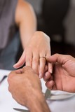 Hand putting a ring on the womans finger