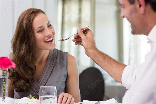 Smiling man feeding woman in the restaurant