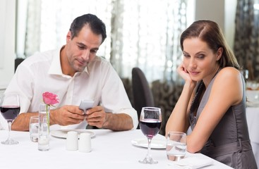 Couple with wine glass and cellphone dining in restaurant