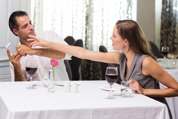 Couple with wine glass and cellphone arguing in restaurant