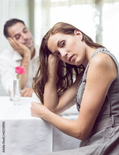 Portrait of bored couple sitting in the restaurant