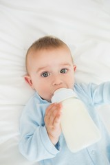 Cute baby boy drinking milk from bottle
