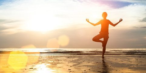 Woman practicing yoga on the beach at sunset.