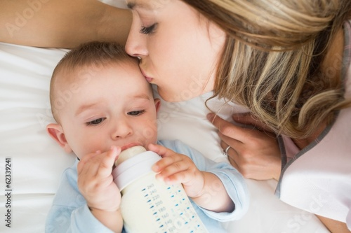 Baby boy drinking milk while mother kissing him