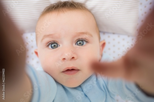 Cute baby boy lying in crib
