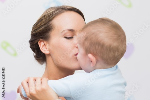 Affectionate mother kissing baby