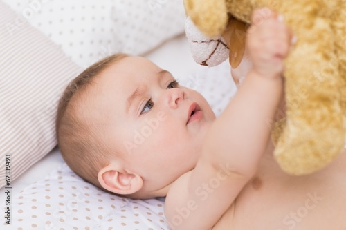 Baby boy playing with teddy bear