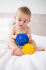 Baby playing with spikey balls