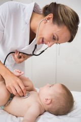 Doctor examining baby boy with stethoscope